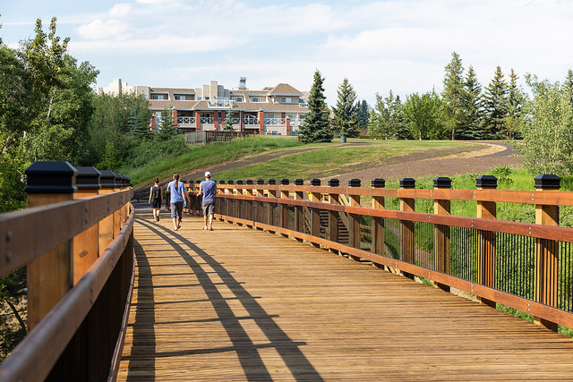 People walking on a wooden bridge at Mill Creek Ravine in Hazeldean Edmonton